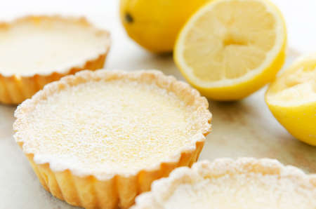 Three lemon tarts dusted with icing sugar, decorated with lemons in the background  photo