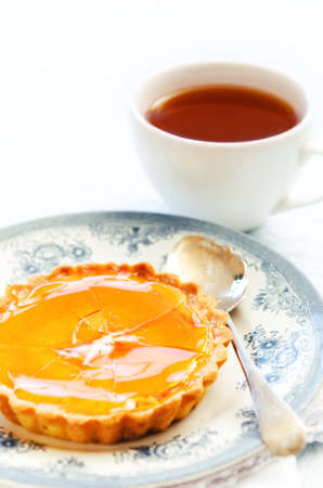 orange tart: Burnt orange tart with a cracked surface served with a cup of tea for a delicious gourmet treat