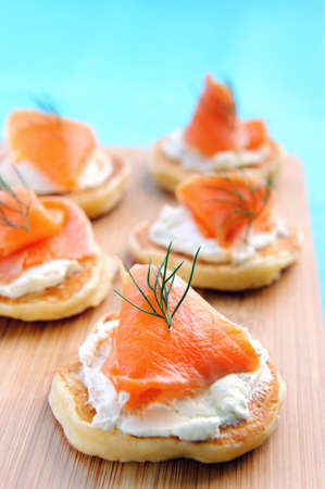 Mini pancakes topped with cream cheese and smoked salmon on a wooden platter  photo
