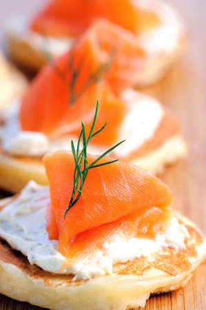 Gourmet smoked salmon and cream cheese blinis on a wooden platter  photo