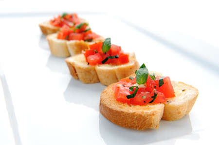 chopped: Italian brushetta; sliced baguette topped with a mixture of chopped tomato, garlic and basil  Stock Photo