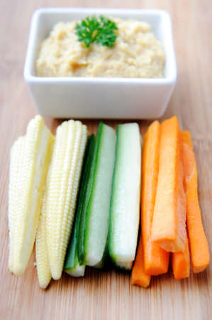 Healthy chickpea dip with colourful raw vegetable sticks  photo