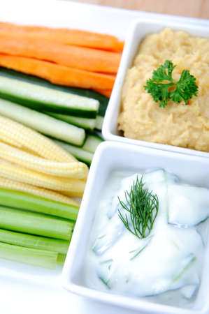 Tzatziki (yoghurt and cucumber) and hummus (chickpea) dips with raw carrot, cucumber, corn and celery