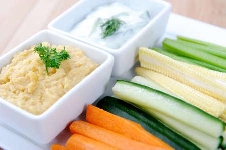 tzatziki: Tzatziki (yoghurt en komkommer) en hummus (kikkererwten) dips met rauwe wortel, komkommer, mais en selderij