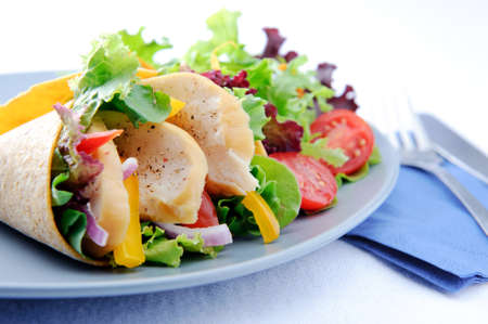 Colourful chicken wrap with plenty of fresh salad and a set of cutlery Stock Photo - 15565892