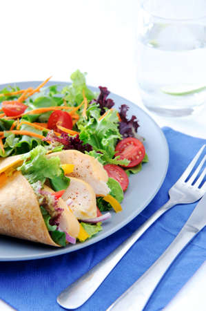 Colourful chicken wrap with plenty of fresh salad and a set of cutlery Stock Photo - 15565896