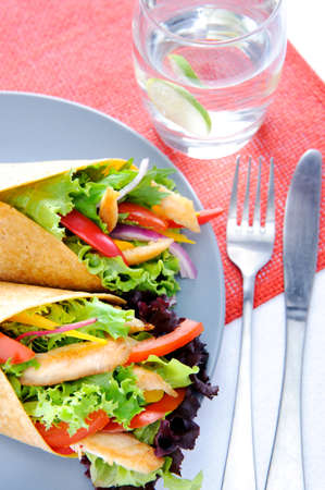 Colourful chicken wrap with plenty of fresh salad and a set of cutlery Stock Photo - 15565872