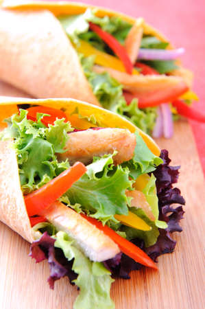 taco tortilla: Healthy chicken strips and fresh salad wrapped in a corn tortilla