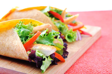 Healthy chicken strips and fresh salad wrapped in a corn tortilla  photo