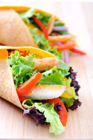 Healthy chicken strips and fresh salad wrapped in a corn tortilla  Stock Photo - 15565893