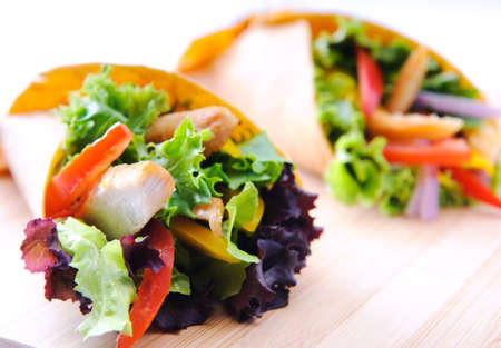 corn tortilla: Healthy chicken strips and fresh salad wrapped in a corn tortilla
