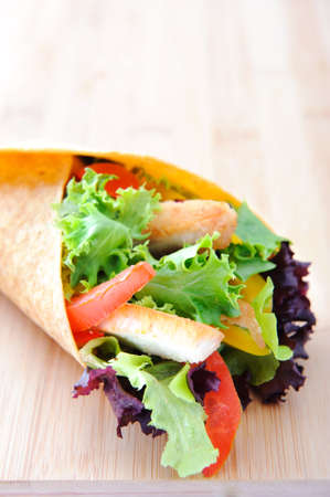 taco tortilla: Chicken strips with fresh salad, bell peppers and tomato slices wrapped in a tortilla