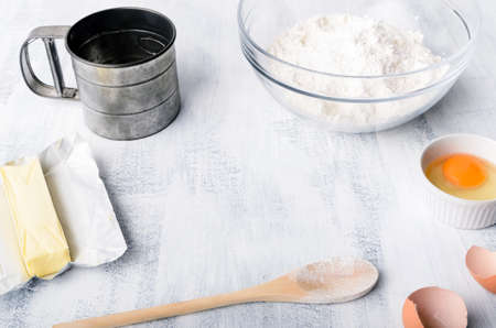 sift: Flour, eggs and baking tools on a board with copy space in the middle Stock Photo