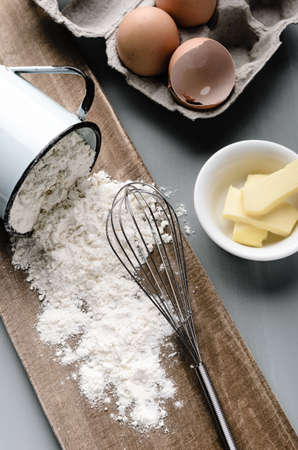 cozimento: Bicarbonato de vida ainda de farinha que derrama fora de um copo, ovos e manteiga em tom Saturado, ilumina