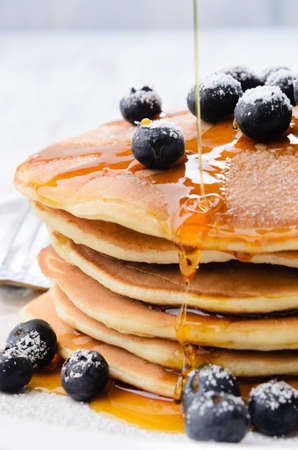 Delicious pancakes stack with fresh blueberries and pouring maple syrup Stock Photo