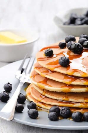 Close up of delicious pancake stack with blueberries and flowing dripping maple syrup photo