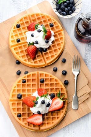 Belgian waffles with blueberries, strawberries and maple syrup photo
