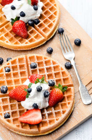 Belgian waffles with fresh fruit and sprinkled with icing sugar photo