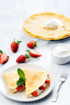 Dessert crepes with strawberry and fresh whipped cream, garnished with mint photo