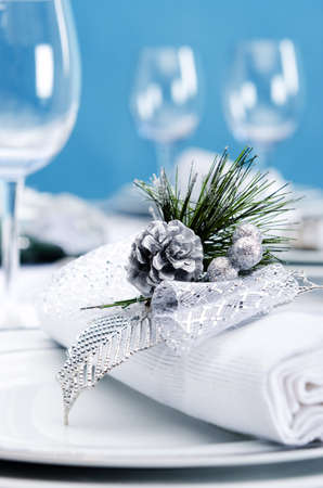 Christmas dinner place setting with silver pinecone decoration napkin with blue background