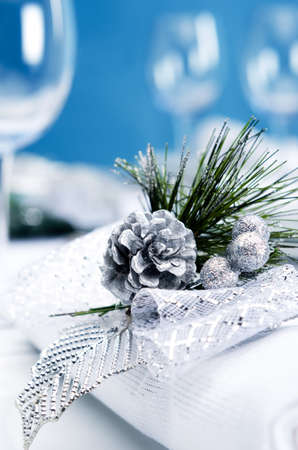 Christmas dinner place setting with silver pinecone decoration napkin with blue background photo