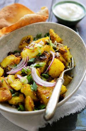 indian spices: Curry aardappelen gekookt in Aziatische Zuid-Indiase kruiden zoals kurkuma en mosterdzaadjes, een elegant etnisch gerecht geserveerd met poppadums en yoghurt