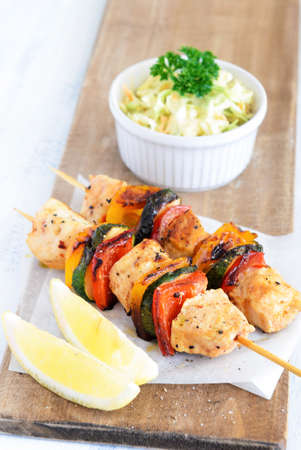 Light summer lunch grilled chicken and vegetable skewers served with coleslaw side salad photo