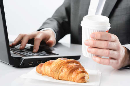 Busy businessman has breakfast coffee and croissant pastry waiting while typing on laptop working photo