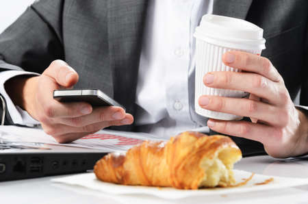 Businessman holds take away coffee cup while working checking emails on his phone with half eaten breakfast croissant in front of him photo
