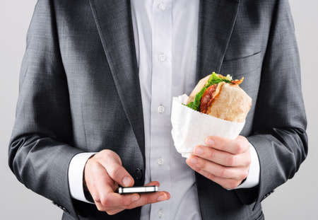 Busy on the go business man in suit texting with smartphone in one hand and holding his BLT ciabatta roll in the other photo
