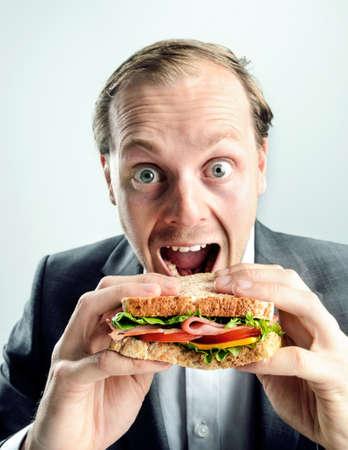 grading: Hombre de negocios en traje con la boca abierta y los ojos comi�ndose su bocadillo comida sana, divertida imagen c�mica con clasificaci�n dividida tono