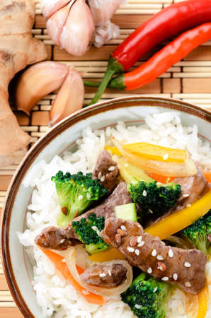 Chinese cuisine beef stir fry with vegetables on white rice, bamboo mat background with raw ingredients photo