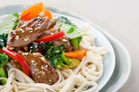 Beef stir-fry with broccoli, carrot, peppers, seasme seed on chinese noodles photo