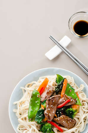 Stir fry beef asian chinese noodles with vegetables and soy dipping sauce, plenty of copy space photo