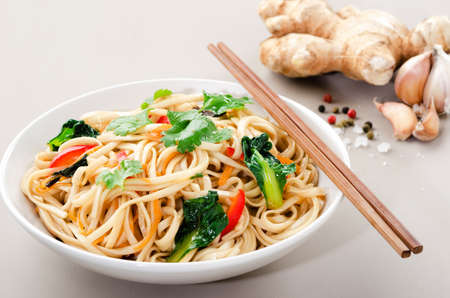 Chinese asian noodles stir fry with vegetables served with a pair of chopsticks photo