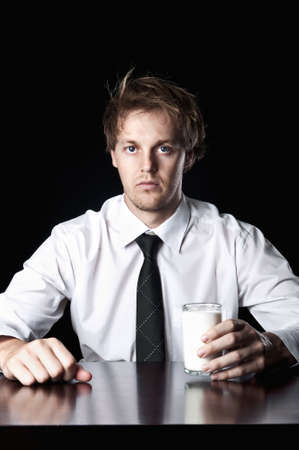 Serious businessman with glass of milk, desaturated with black background Stock Photo - 16253011