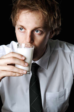 Serious businessman drinking glass of milk, desaturated with black background Stock Photo - 16253016