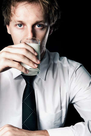 Serious businessman drinking glass of milk, desaturated with black background Stock Photo - 16253033