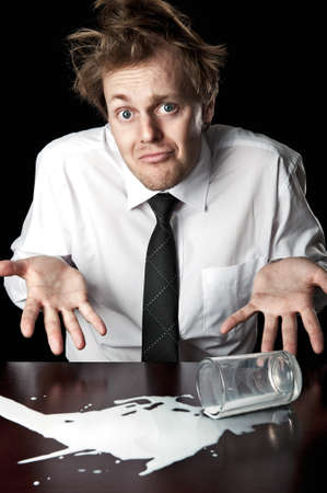 Businessman shrugs and helpless after knocking over glass of milk on table, desaturated with black background photo