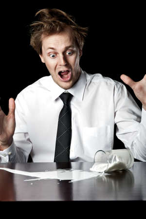 Businessman knocks over glass of milk, exclaims in horror, conceptual image desaturated with black background Stock Photo - 16253015