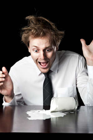 Businessman knocks over glass of milk, exclaims in horror, conceptual image desaturated with black background Stock Photo - 16253025
