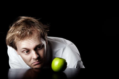 Businessman desaturated, lifeless and unmotivated looking at bright green apple for inspirational idea spark, abstract business concept photo