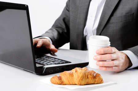 Business man holds coffee while working at desk with breakfast croissant, selective focus on hand photo