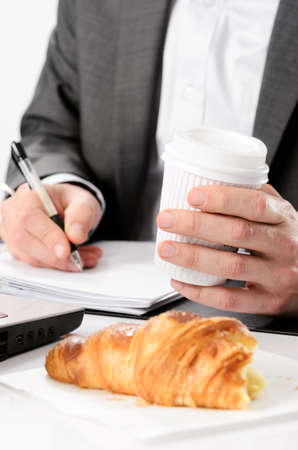 Man in suit writes while having a breakfast croissant and drinks coffee photo
