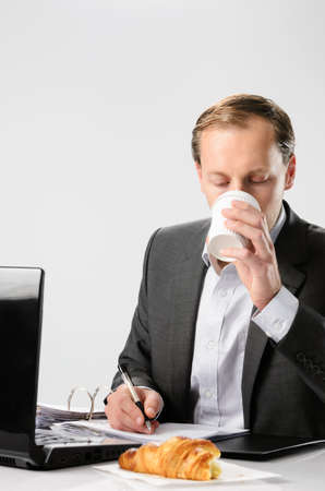 Businessman drinks coffee while working hard signing documents and contracts photo