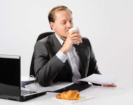 Businessman drinks enjoys his morning coffee and croissant before he starts work photo