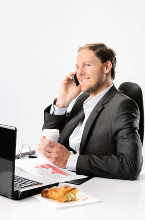 Man in business suit talks on mobile cell phone while drinking coffee and eating croissant pastry at his desk with laptop and documents photo