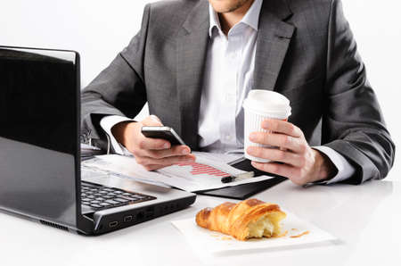 Anonymous business man types on smartphone while having a coffee and snack at his desk with laptop computer and documents photo