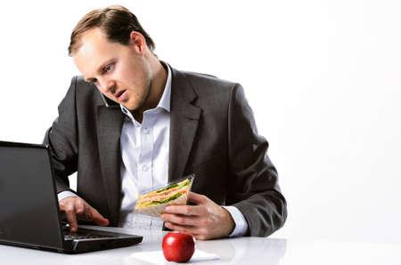 바쁜 근면 한 사업가 멀티 태스킹, 노트북 컴퓨터에서 모바일 휴대 전화의 입력에 대한 얘기와 빨간 사과와 건강 샌드위치 점심을 먹고