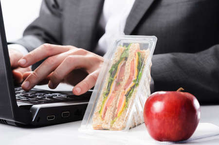 out to lunch: Corporate business worker working on computer, too busy to eat healthy take away lunch sandwich and fresh red apple